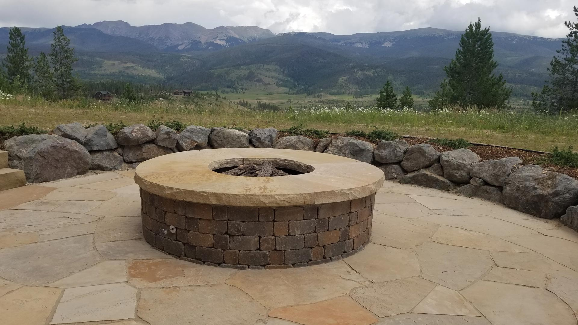 A round fire pit with a flagstone patio and rock retaining wall overlooking the mountains in Winter Park, CO.