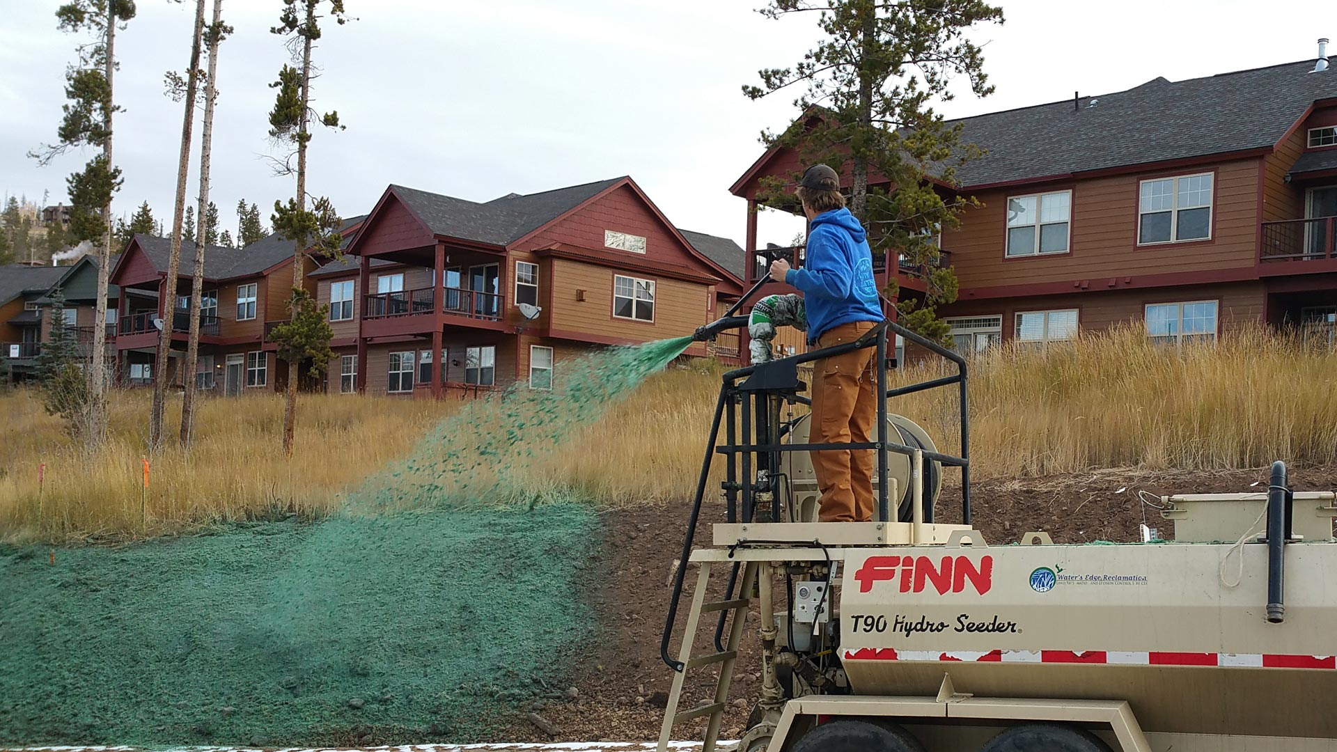 Hydro seeding truck in front of a commercial property spraying seed on a slope.