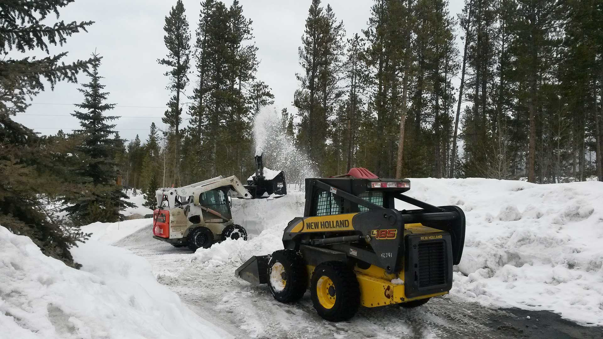 Company skid loaders clearing snow from a customer's property.