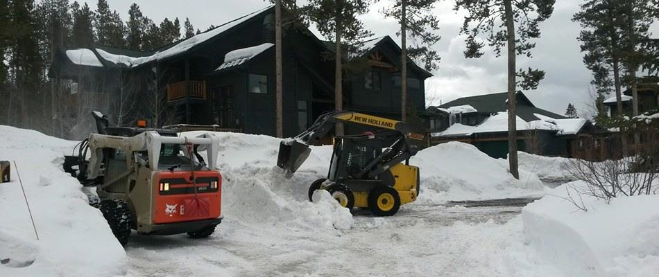 Two of our team members removing snow from a parking lot of a client in Fraser.